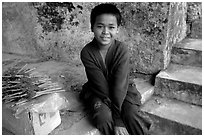Boy sells incence sticks at the entrance of a shrine, Pak Ou. Laos (black and white)