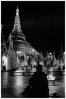 Praying at the wish-fullfilling place by night , Shwedagon Paya. Yangon, Myanmar (black and white)