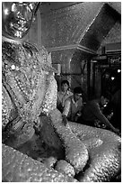 Adding golden leaves to the venerated Mahamuni image. Mandalay, Myanmar ( black and white)