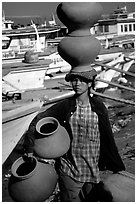 Carrying many jars. Mandalay, Myanmar (black and white)