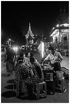 Women eating at street stall at night with Shwedagon Pagoda in background. Yangon, Myanmar ( black and white)