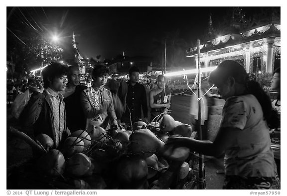 Customers waiting for coconuts to be cut on the street. Yangon, Myanmar (black and white)
