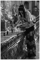 Woman lighting candles, Shwedagon Pagoda. Yangon, Myanmar ( black and white)
