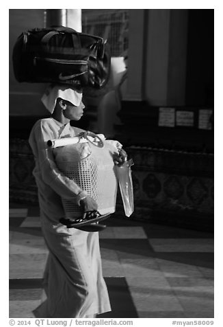 Nun carrying lots of luggage, Shwedagon Pagoda. Yangon, Myanmar (black and white)