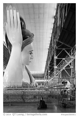 Monk and reclining Buddha statue housed in large metal shed, Kyauk Htat Gyi Pagoda. Yangon, Myanmar (black and white)