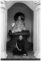 Monk meditating in alcove with Buddha statue, Shwedagon Pagoda. Yangon, Myanmar ( black and white)
