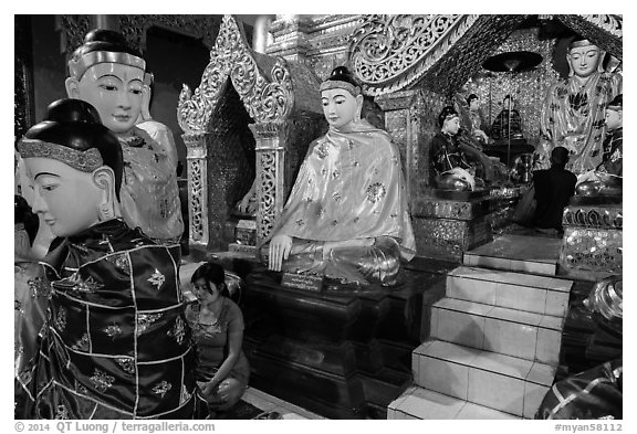 Woman and monk in pavillion surrounded by Buddha statues. Yangon, Myanmar (black and white)