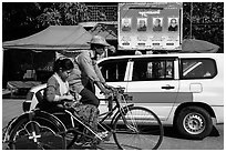 Trishaw, taxi, and billboard promoting monks. Yangon, Myanmar ( black and white)
