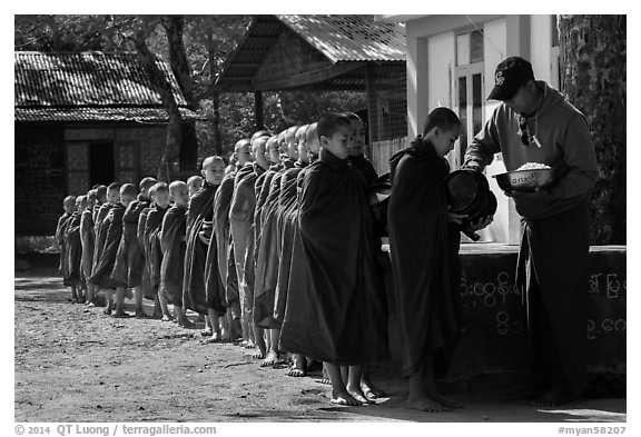 Buddhist novices lining up to receive rice for lunch, Nyaung U. Bagan, Myanmar (black and white)