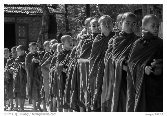 Novices lining up with alms bowls, Nyaung U. Bagan, Myanmar (black and white)