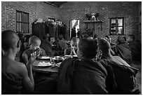Buddhist novices pray at table before eating lunch, Nyaung U. Bagan, Myanmar ( black and white)