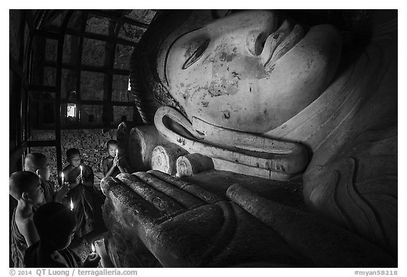 Young monks with candles worship Shin Bin Thal Yaung reclining Budddha. Bagan, Myanmar (black and white)