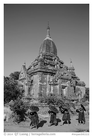 Four novices walk next to temple. Bagan, Myanmar (black and white)
