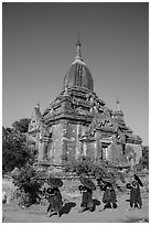 Four novices walk next to temple. Bagan, Myanmar ( black and white)