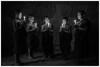 Five novices standing in circle inside temple with candles. Bagan, Myanmar ( black and white)