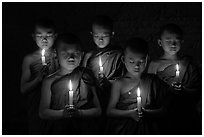 Young buddhist monks holding candles with eyes closed. Bagan, Myanmar ( black and white)