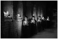Buddhist novices in temple illuminated with candles. Bagan, Myanmar ( black and white)