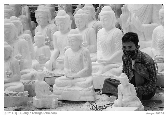 Man working amongst many  buddha statues on Marble street workshop. Mandalay, Myanmar (black and white)