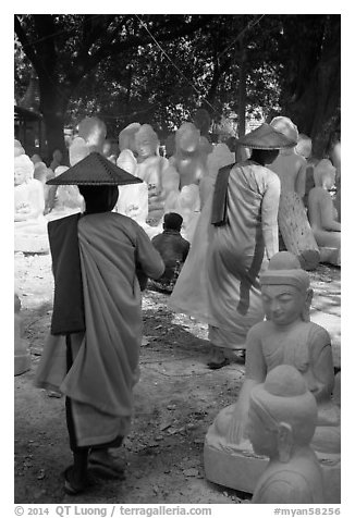 Nuns walk between buddha statues on Marble street. Mandalay, Myanmar (black and white)
