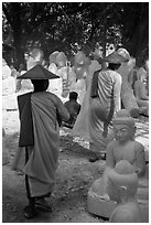 Nuns walk between buddha statues on Marble street. Mandalay, Myanmar ( black and white)