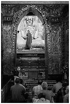 Monk applying gold leaf to Buddha statue in Mahamuni Pagoda. Mandalay, Myanmar ( black and white)
