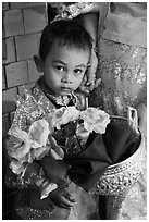 Child carrying offering bowl and flowers for novitiation ceremony, Mahamuni Pagoda. Mandalay, Myanmar ( black and white)