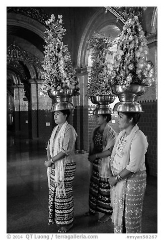 Women carry elaborate flower offerings on their head, Mahamuni Pagoda. Mandalay, Myanmar (black and white)