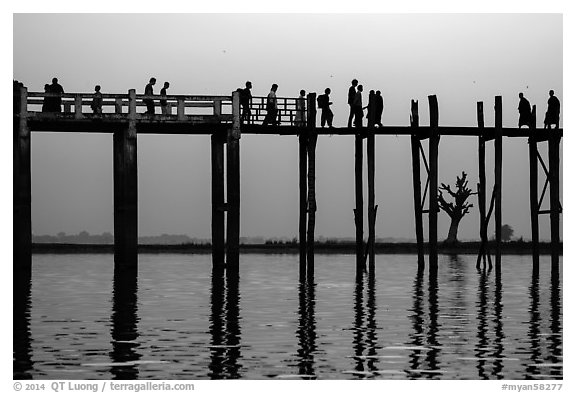 U Bein Bridge with monks and visitors strolling at dusk. Amarapura, Myanmar (black and white)