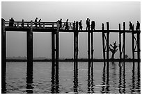 U Bein Bridge with monks and visitors strolling at dusk. Amarapura, Myanmar ( black and white)
