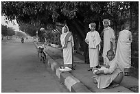 Nuns waiting for ride on sidewalk. Mandalay, Myanmar ( black and white)