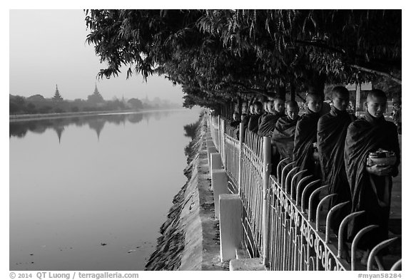 Monks walking in line in alm bowls near Mandalay Fort moat. Mandalay, Myanmar (black and white)