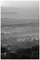 Fog shrouded plain below Mandalay Hill at sunrise. Mandalay, Myanmar ( black and white)
