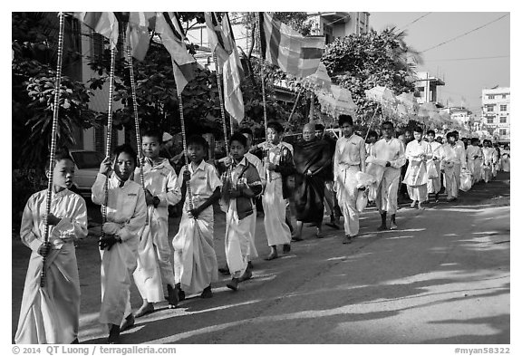 Children carry Buddhist flags ahead of alms procession. Mandalay, Myanmar (black and white)