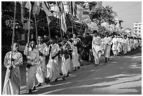 Children carry Buddhist flags ahead of alms procession. Mandalay, Myanmar ( black and white)