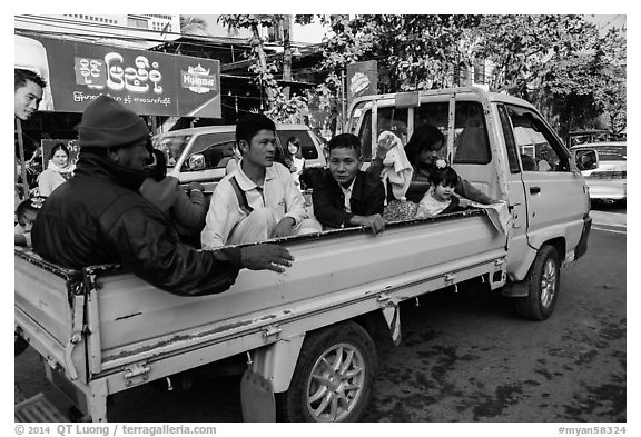 Families riding on back of pick-up truck. Mandalay, Myanmar (black and white)