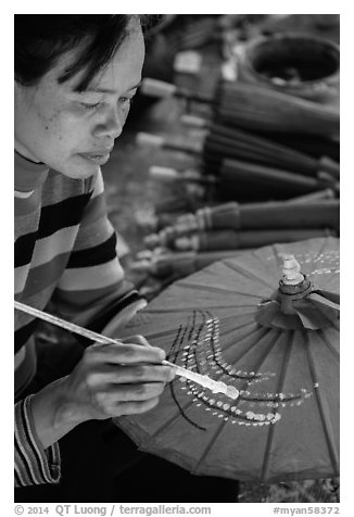 Woman painting the paper sun umbrellas carried by the monks. Pindaya, Myanmar (black and white)