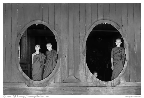 Monks standing in oval windows, Shweyanpyay Monastery, Nyaung Shwe. Inle Lake, Myanmar (black and white)