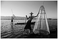 Intha fishermen with conical baskets in warm afternoon light. Inle Lake, Myanmar ( black and white)