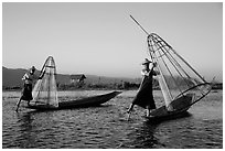 Intha fishermen row with leg and hold conical baskets. Inle Lake, Myanmar ( black and white)