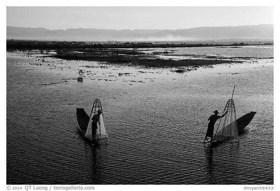 Intha fishermen row with backlit conical nets. Inle Lake, Myanmar (black and white)