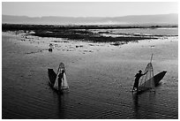 Intha fishermen row with backlit conical nets. Inle Lake, Myanmar ( black and white)