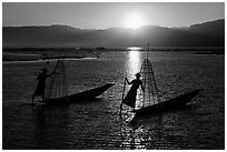 Intha fishermen row with leg with setting sun. Inle Lake, Myanmar ( black and white)