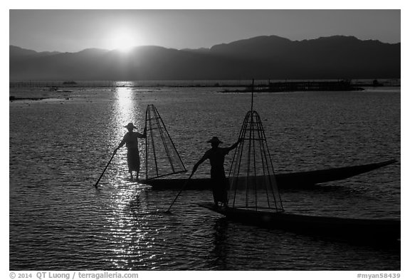 Intha fishermen on long flat-bottomed boats at sunset. Inle Lake, Myanmar (black and white)