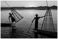 Intha fishermen lifting traditional conical net at sunset. Inle Lake, Myanmar ( black and white)