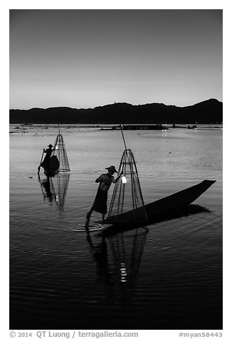 Intha fishermen carrying lanterns at dusk. Inle Lake, Myanmar (black and white)