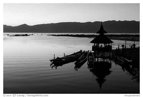 Deck, pavillion, and longtail boats at sunset. Inle Lake, Myanmar (black and white)