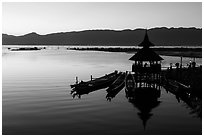 Deck, pavillion, and longtail boats at sunset. Inle Lake, Myanmar ( black and white)