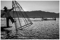 Intha fisherman standing on boat stern to lift net basket. Inle Lake, Myanmar ( black and white)