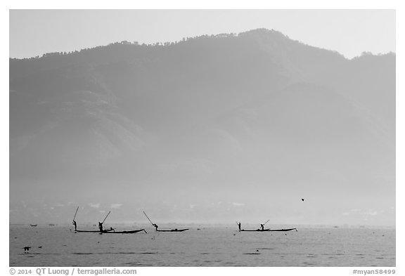 Intha fishermen in the distance using spears to stir fish, below tall hills. Inle Lake, Myanmar (black and white)