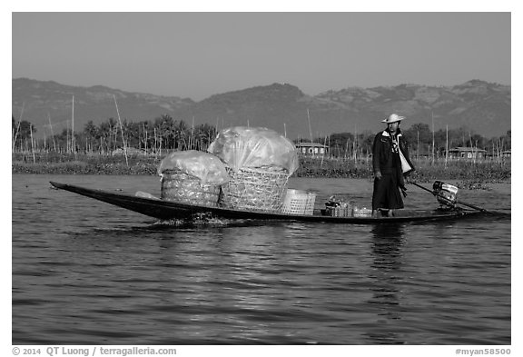 Man transporting baskets on boat. Inle Lake, Myanmar (black and white)